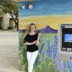 Presley Rumsey pictured with Texas Trust Credit Union painted mural in San Angelo, Texas